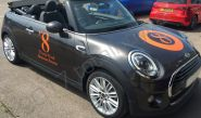 MINI Convertible fully wrapped in a pearlescent black vinyl car wrap with gloss orange cut vinyl graphics
